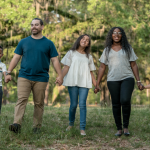 A multiracial family holds hands in a rural setting, with a large tree behind them.